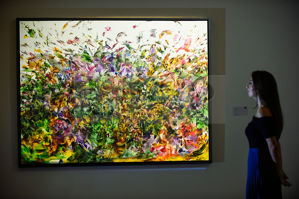 """© Licensed to London News Pictures. 18/10/2019. LONDON, UK. A staff member poses with """"Stardust"""", 2011, by Ali Banisadr (Est. GBP280,000-350,000).  Preview of Islamic, Indian and Middle Eastern art to be auctioned at Sotheby's, New Bond Street, on 22 and 23 October.  Photo credit: Stephen Chung/LNP"""