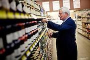 Darrell Corti straightens some shelves at Corti Bros. in Sacramento, Calif., March 3, 2012.