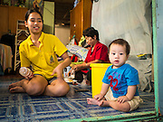 06 FEBRUARY 2015 - BANGKOK, THAILAND: A woman and her son in their home near Santa Cruz Catholic Church in the Thonburi section of Bangkok. Now the neighborhood around the church is known for the Thai adaptation of Portuguese cakes baked in the neighborhood. Several hundred Siamese (Thai) Buddhists converted to Catholicism in the 1770s. Some of the families started baking the cakes. When the Siamese Empire in Ayutthaya was sacked by the Burmese, the Portuguese and Thai Catholics fled to Thonburi, in what is now Bangkok. The Portuguese established a Catholic church near the new Siamese capital. There are still a large number of Thai Catholics living in the neighborhood around the church.       PHOTO BY JACK KURTZ