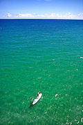 Aerial view of Woman paddling surfboard on wide open sea.  Clear water from green to blue on the distant horizon