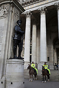 Two officers on horses with the mounted City Police, patrol beneath the war memorial and columns of Conhill Exchange in the City of London, the capital's financial district, on 14th March 2018, in London England.