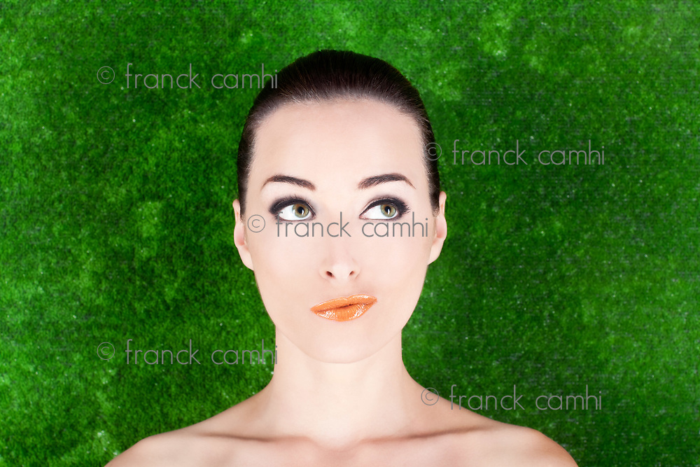 Closeup portrait of an expressive thoughtful woman looking up in studio against green