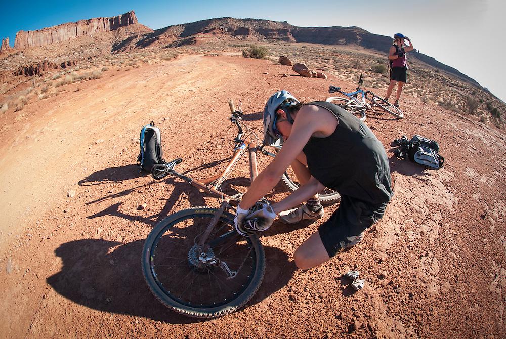 Riders tune up thier mountain bikes while touring the White Rim Trail near Moab, Utah.