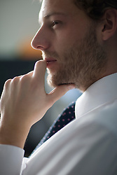 Close up of young businessman with finger on lips