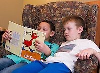 "Nehemiah and Josiah find a comfy chair and red ""Fox in Socks"" by Dr. Seuss at the Gilford Library during Read Across America on Wednesday afternoon.  (Karen Bobotas/for the Laconia Daily Sun)"