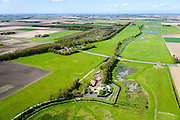 Nederland, Flevoland, Noordoostpolder, 07-05-2015; Schokland, dorp en voormalig eiland in de Zuiderzee, gezien vanuit het Zuiden. Middelbuurt met hervormde kerk, onderdeel van het museum Schokland. Schokland maakt deel uit van de UNESCO Werelderfgoedlijst. Het verlagen van de grondwaterspiegel in de Noordoostpolder leidt tot inklinking waardoor het eiland steeds lager komt te liggen. Om verder wegzinken te voorkomen een hydrologische zone aangelegd.<br /> Village and former island, seen from the south. Part of the UNESCO World Heritage List. The center is the Reformed Church. Lowering the groundwater level in the Noordoostpolder leads to subsidence and causes the island the sink away. In order to prevent further decline a hydrological zone has been created.<br /> luchtfoto (toeslag op standard tarieven);<br /> aerial photo (additional fee required);<br /> copyright foto/photo Siebe Swart
