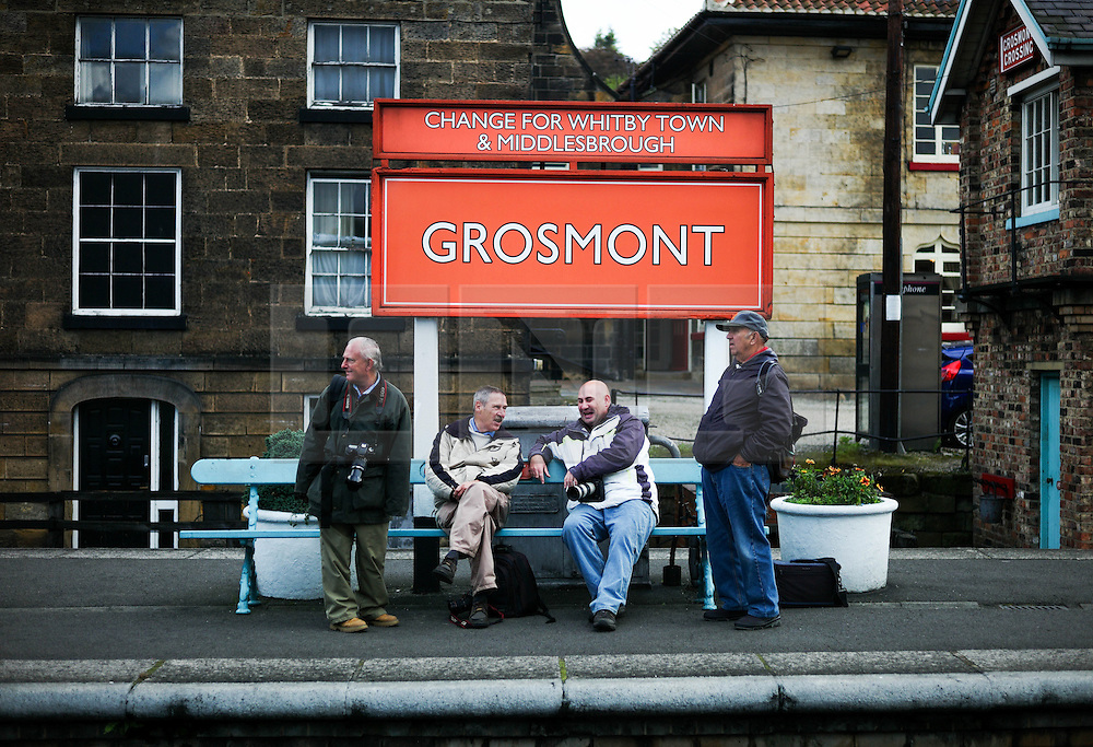 © Licensed to London News Pictures. <br /> 01/10/2016. <br /> Grosmont, UK.  <br /> <br /> A group of friends sit on the platform at Grosmont station as they attend the North Yorkshire Moors Railway Autumn Steam Weekend. <br /> The hugely popular railway line runs a service between Pickering and Whitby through the picturesque North yorkshire countryside and attracts thousands of visitors each year. <br /> <br /> Photo credit: Ian Forsyth/LNP