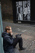 Lone man smokes a cigarette opposite contemporary poster of young people, in London's Carnaby Street