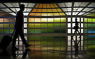 Passengers shuffle to and from their flights amid a Helmut Jahn designed sculpture of lights at Terminal 1 at Chicago's O'Hare Airpor.
