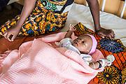 A baby lying next to her mother on the children's ward. St Walburg's Hospital, Nyangao. Lindi Region, Tanzania.
