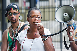 """Zimmerman's trial began on June 10, 2013, in Sanford. On July 13, 2013, he was found not guilty of second-degree murder and of manslaughter charges of Trayvon Martin.<br /> A demonstrator speaks on the megaphone while a woman holds a placard reading """"Child Killer"""" outside the American Embassy to protest the recent Trayvon Martin's Verdict, London, United Kingdom<br /> Tuesday, 16 July 2013<br /> Picture by Piero Cruciatti / i-Images"""