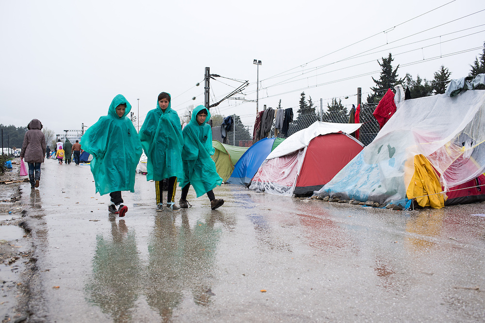 Three girls in green raincoats walk under the rain in the transit camp of Idomeni, Greece. <br /> <br /> Thousands of refugees are stranded in Idomeni unable to cross the border. The facilities are stretched to the limit and the conditions are appalling.