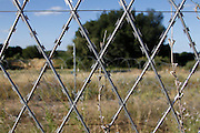 Holes in the razor wire fence that forms the border between Zimbabwe and South Africa on the Limpopo river near Beitbridge, South Africa<br /> <br /> Photograph by Zute Lightfoot