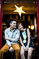 A young man and woman sit outside of Tadioto, a popular bar in Hanoi, Vietnam. Clothes by Kilomet 109 and Chula.