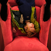 Micah Goodrich sleeps collapsed on the red chair after of his first day of skiing in Washington.
