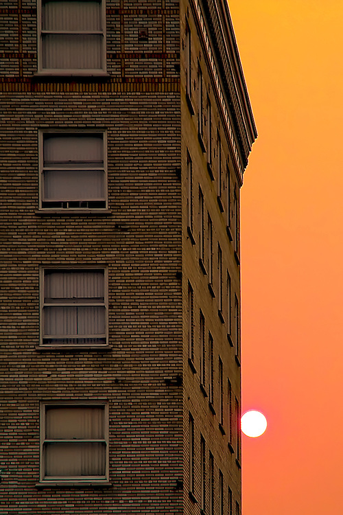 Setting sun next to residential hotel in downtown Oakland, CA.  Copyright 2008 Reid McNally.