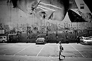 A girl walks by a huge artwork from JR on a wall of SoHo in Manhattan, New York