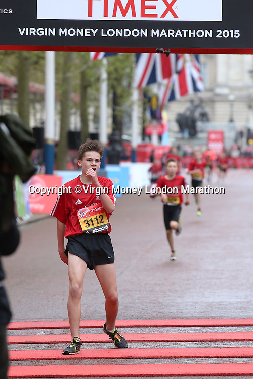 A competitor crosses the line to in the Boys U13 race in the Virgin Giving Mini London Marathon, Sunday 26th April 2015.<br /> <br /> Scott Heavey for Virgin Money London Marathon<br /> <br /> For more information please contact Penny Dain at pennyd@london-marathon.co.uk