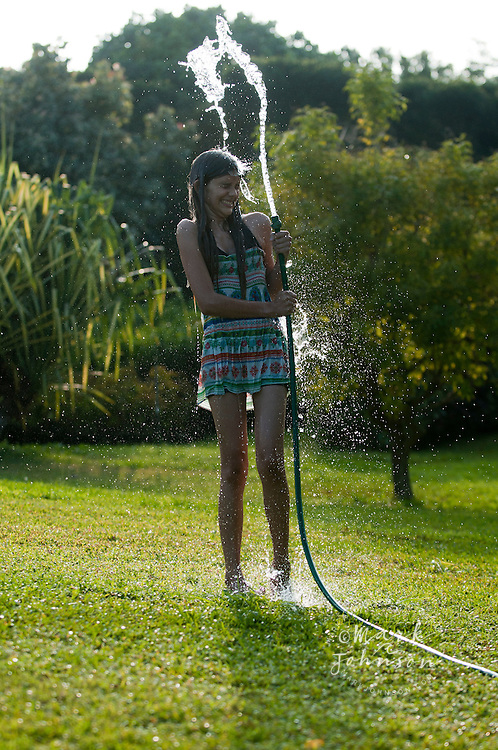 13 year old girl playing with garden hose, Kauai, Hawaii
