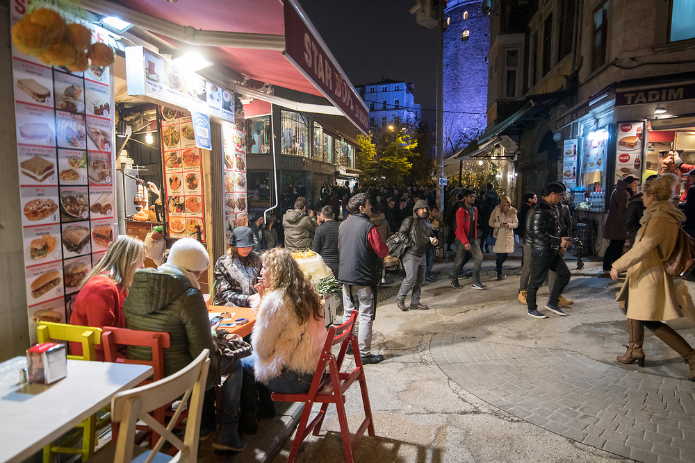 A group of people gather together at a table outside of resturant to grab a bite to eat on the busy streets of Istanbul, Turkey