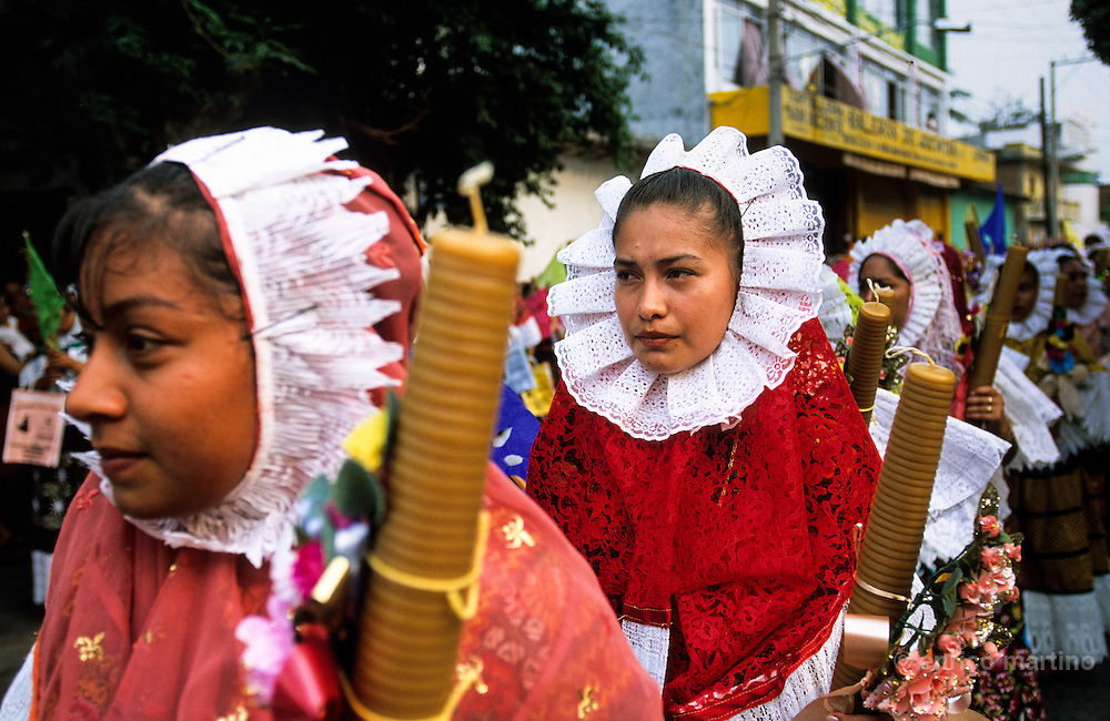 "Juchitàn, Vela Cheguigo. Tehuanas with traditional ""Huipil Grande"", often worn as hood. The tehuanas are the archetype of an ancient and legendary Mexico, told in the murales of Diego Rivera and impersonated also by Frida Kalho that often wore these traditional dresses. But these showy dresses, and the rich golden ornaments that accompany them, are above all an instrument of auto-representation for these active women which the control of the local markets confers an independent economic power that is reflected in the self confidence. Even in the development of the festivities, where the women often dance a lot among them while the men remain seated watching."