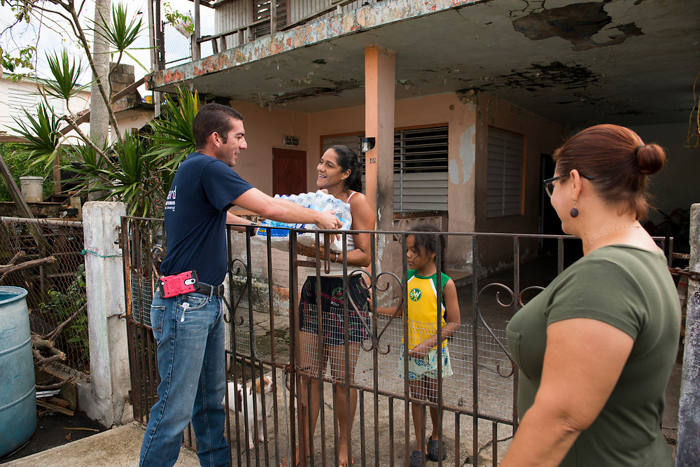 Toa Baja, PR, November 10, 2017--Jesús Pagán Torres, left, and Moriama Cortés, right, are part of a team of faculty and staff of Escuela Delia Cabán who continue to distribute water and emergency relief in Tao Baja, PR neighborhoods still without power and water 50 days after Hurricane Maria.  Escuela Delia Cabán has served as a distribution point for the Puerto Rico Recovery Fund's emergency relief efforts since it was established days after the storm hit September 20, 2017.  Photo by Lori Waselchuk/BRAF