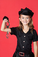 Portrait of young girl in police costume holding handcuffs against red background