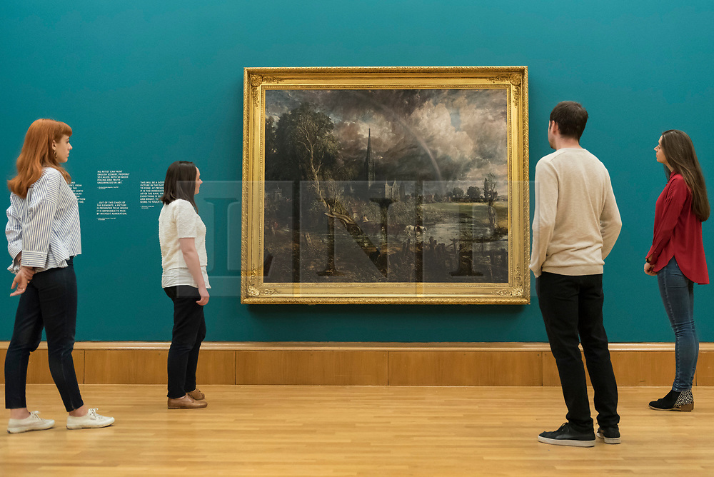 """© Licensed to London News Pictures. 25/05/2018. LONDON, UK. Staff members view """"Salisbury Cathedral from the Meadow"""", 1831, by John Constable at the preview of Fire and Water, a display of masterpieces by Constable and Turner at Tate Britain.  On display for the first time in 180 years alongside each other are """"Salisbury Cathedral from the Meadow"""", 1831, by John Constable and """"Caligula's Palace and Bridge"""", 1831, by J.M.W. Turner.  The works will on display 26 May 208 to July 2019.  Photo credit: Stephen Chung/LNP"""
