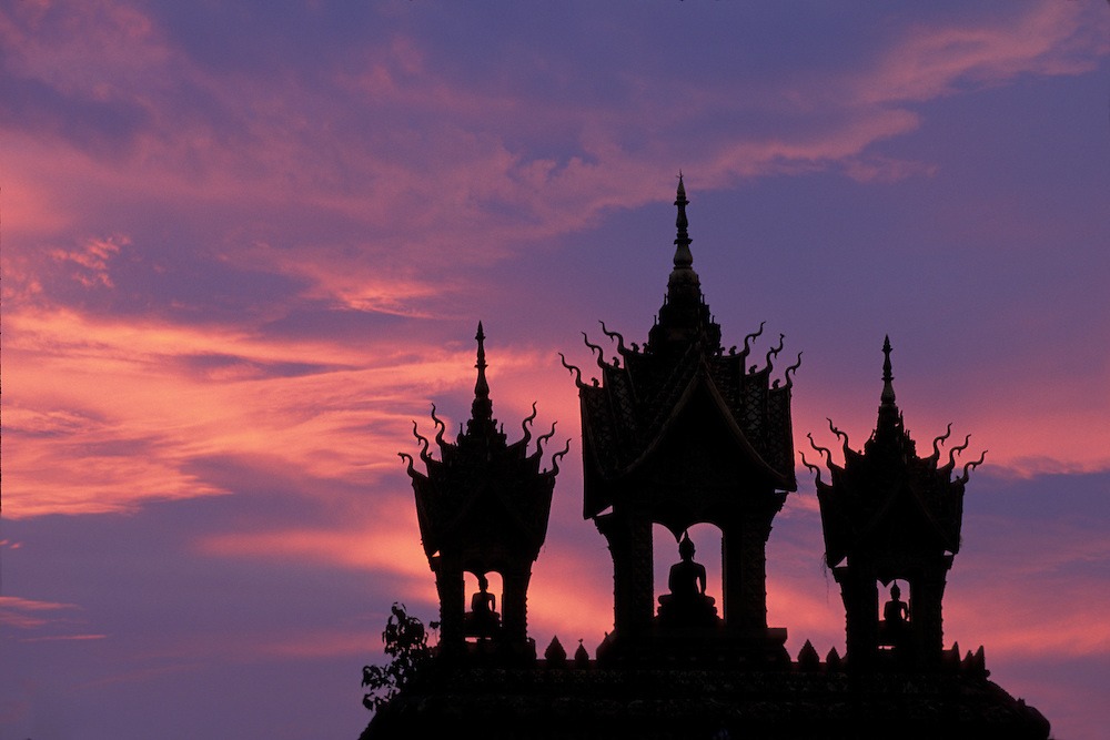 Asia, Laos, Vientiane, Setting sun silhouettes gate outside Pha That Luang Temple on summer evening