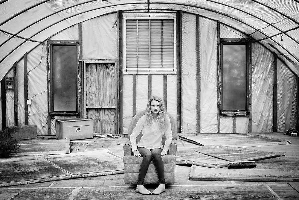 A 15-year-old blond teenager wearing a white button down shirt and jeans sits in a moldy chair in an abandoned greenhouse in Apex, NC.