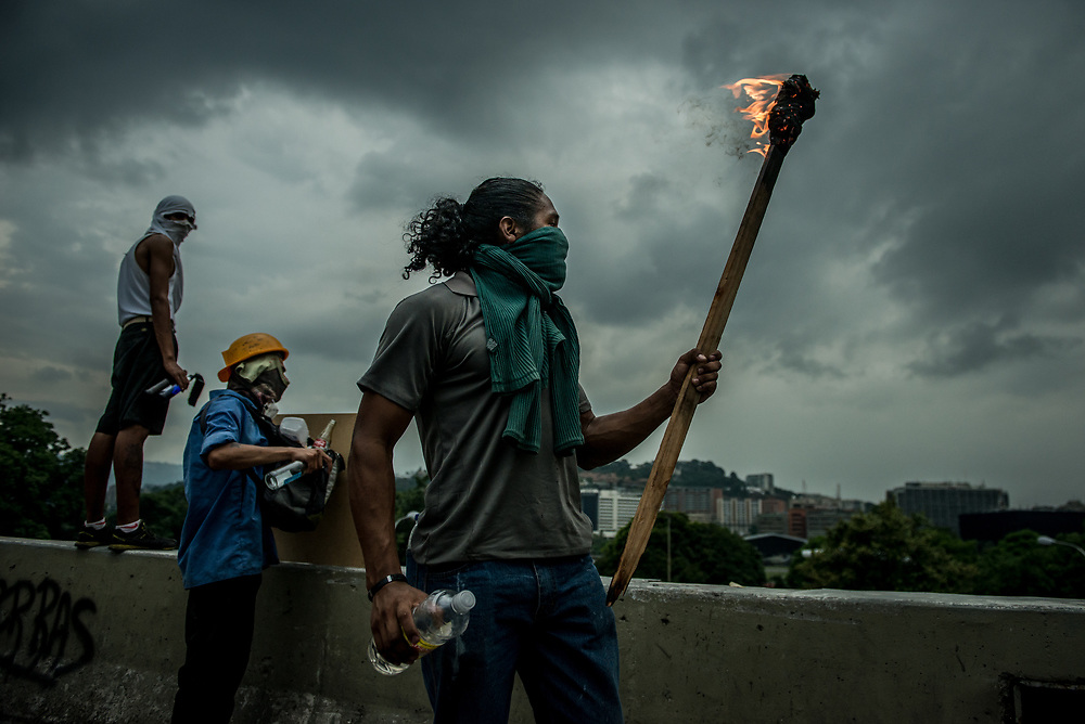 CARACAS, VENEZUELA - MAY 10, 2017:  Anti-government protesters carry torches as the sun sets and they fight to take control of Francisco Fajardo highway, from National Guard soldiers . The streets of Caracas and other cities across Venezuela have been filled with tens of thousands of demonstrators for nearly 100 days of massive protests, held since April 1st. Protesters are enraged at the government for becoming an increasingly repressive, authoritarian regime that has delayed elections, used armed government loyalist to threaten dissidents, called for the Constitution to be re-written to favor them, jailed and tortured protesters and members of the political opposition, and whose corruption and failed economic policy has caused the current economic crisis that has led to widespread food and medicine shortages across the country.  Independent local media report nearly 100 people have been killed during protests and protest-related riots and looting.  The government currently only officially reports 75 deaths.  Over 2,000 people have been injured, and over 3,000 protesters have been detained by authorities.  PHOTO: Meridith Kohut