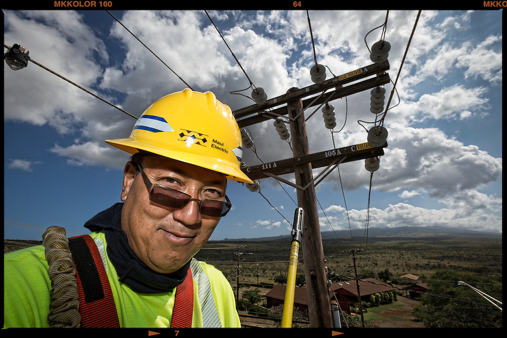 Lloyd Adams, MECO Lineman Foreman, pauses for a portrait high in the bucket while testing the line outside Kaunakakai.