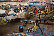 A woman seating on a matress in Mopti's harbour. At the confluence of the Niger and the Bani rivers, between Timbuktu and Segou, Mopti is the second largest city in Mali, and the hub for commerce and tourism in this west-african landlocked country.