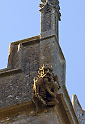 Gargoyle carved stone grotesque carving of a figure on St Peter's church in Winchcombe, Gloucestershire, England