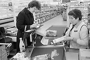 Writing a cheque at a checkout. Sainsbury's, Sheffield.