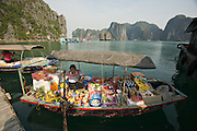 Halong Bay. Women selling all kinds of things to eat and drink from aboard a rowing boat.