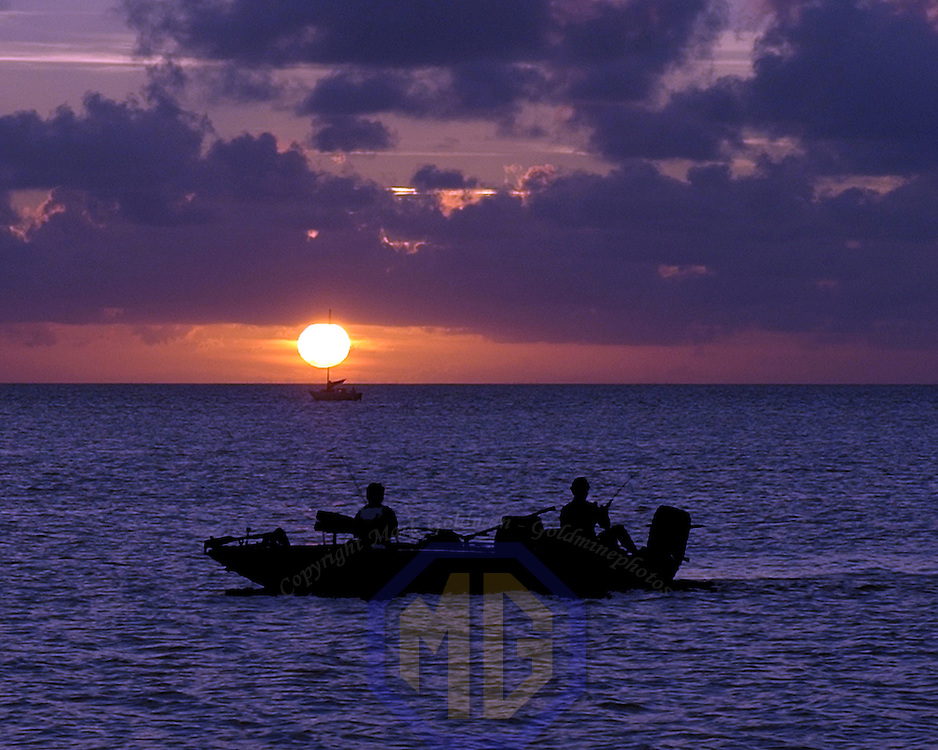 30 July 2004:  A small boat with two fisherman  fish in the Albemarle Sound as the sun sets on July 30, 2004 in Cape Hatteras, North Carolina.