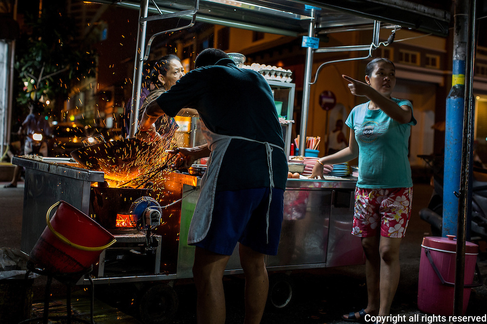 A street food hawker fries char koay teow over charcoal. Kimberley Street, George Town, Malaysia July, 2013