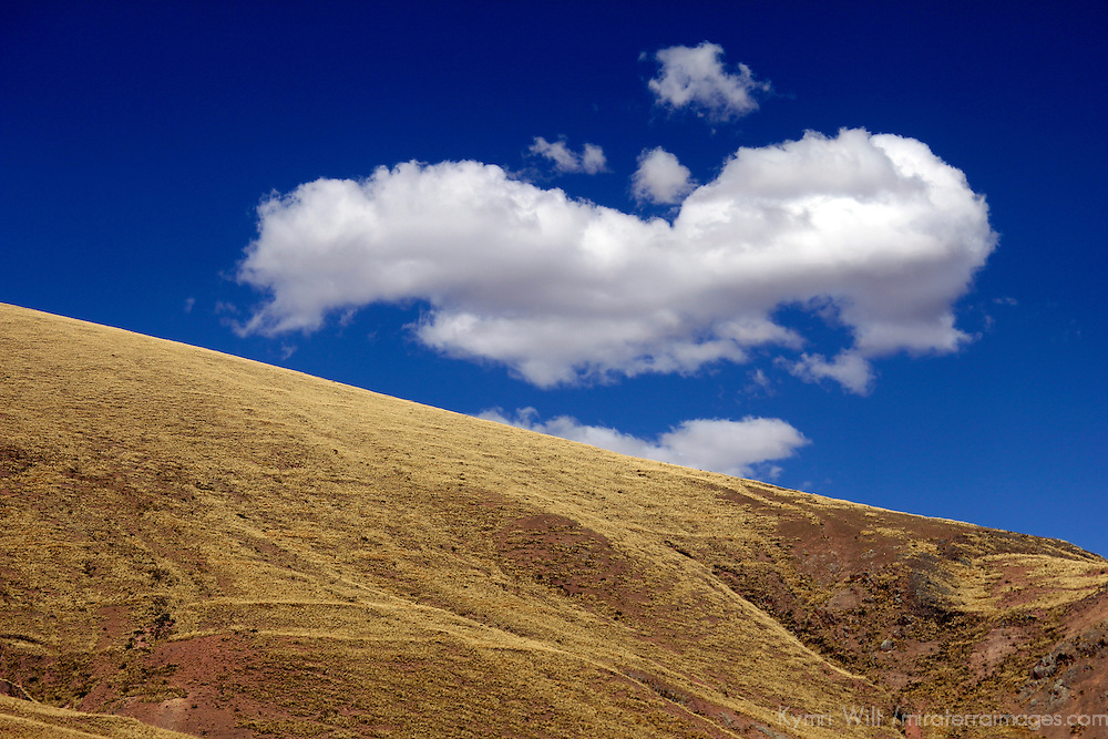 South America, Peru. A puffy white cloud in a blue sky sets the backdrop for the sloping Andean landscape.