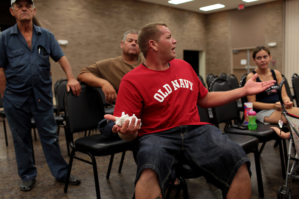 Commercial shrimp boat captains Joseph Latapie, 72, left, Travis Latapie, Chris Battle and his wife Cierra Battle, listen to the BP representative answer questions about the BP oil spill in the Gulf of Mexico at a Public Meeting at the Frederick J. Sigur Civic Center Ballroom in Chalmette, Louisiana on May 24th, 2010.
