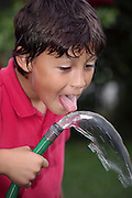 Young boy playing with a garden hose - EXCLUSIVELY AVAILABLE HERE