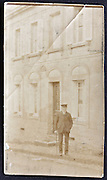 1900s photograph of elderly man standing by his house