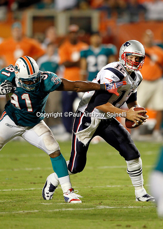 New England Patriots quarterback Tom Brady (12) gets chased by Miami Dolphins linebacker Cameron Wake (91) during the NFL week 1 football game against the Miami Dolphins on Monday, September 12, 2011 in Miami Gardens, Florida. The Patriots won the game 38-24. ©Paul Anthony Spinelli