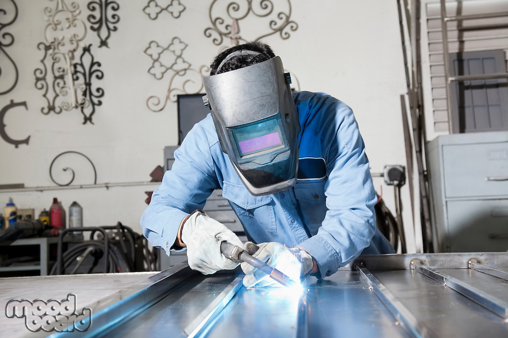 Young man welding in metal workshop