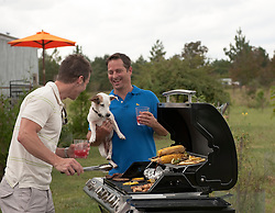 Two men enjoying themselves at a barbecue while a dog looks at the food on the grill
