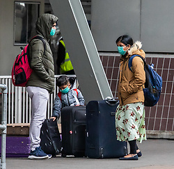© Licensed to London News Pictures. 10/03/2020. London, UK. A family in masks arrive at Heathrow Terminal 4 where flights to Italy continue to run as British Airways cancels all flights to and from Italy over fears of the Coronavirus disease. Photo credit: Alex Lentati/LNP