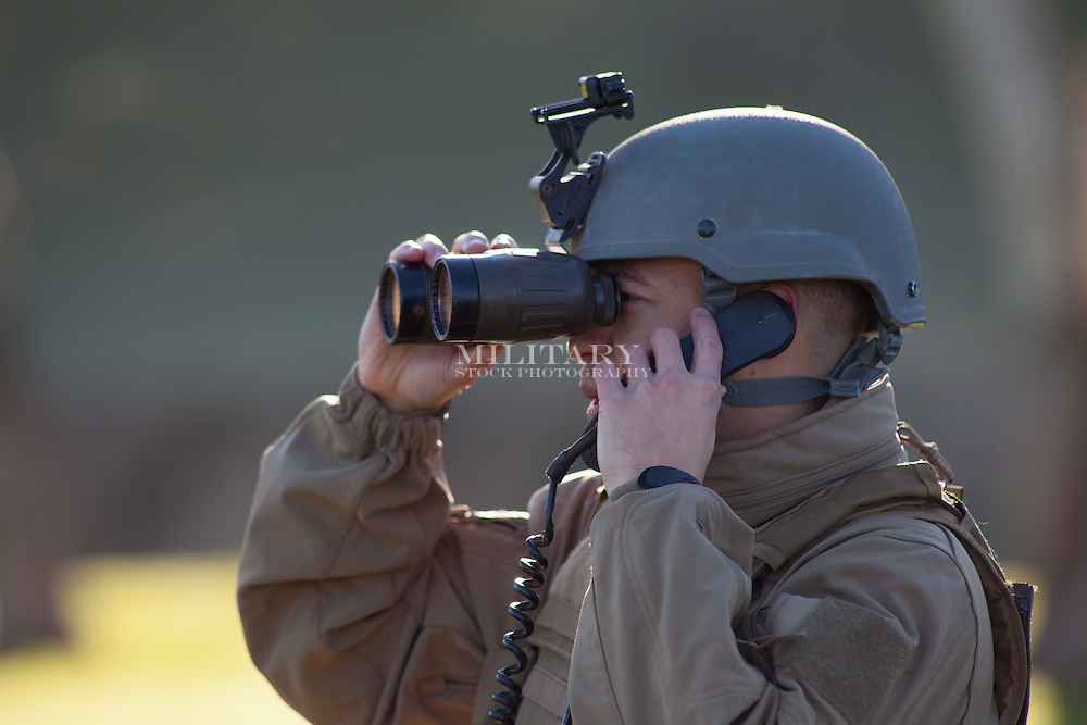 Soldier in desert with M22 Steiner 7X50 military binoculars with anti-laser filter.  Model-released.