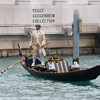 VENICE, ITALY - FEBRUARY 19:  A gondolier dressed with 1700 costumes crosses the Grand Canal (Canal Grande) in front of the Peggy Guggenheim on February 19, 2012 in Venice, Italy.  The annual festival, which lasts nearly three weeks, will see the streets and canals of Venice filled with people wearing highly-decorative and imaginative carnival costumes and masks.  (Photo by Marco Secchi/Getty Images)