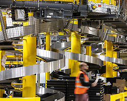 """© Licensed to London News Pictures . 04/12/2019. Manchester , UK . Spiral conveyor belts carry containers of stock from a lower level of the warehouse up to the level above . Inside the """"MAN1"""" Amazon fulfilment centre warehouse at Manchester Airport in the North West of England . Photo credit : Joel Goodman/LNP"""