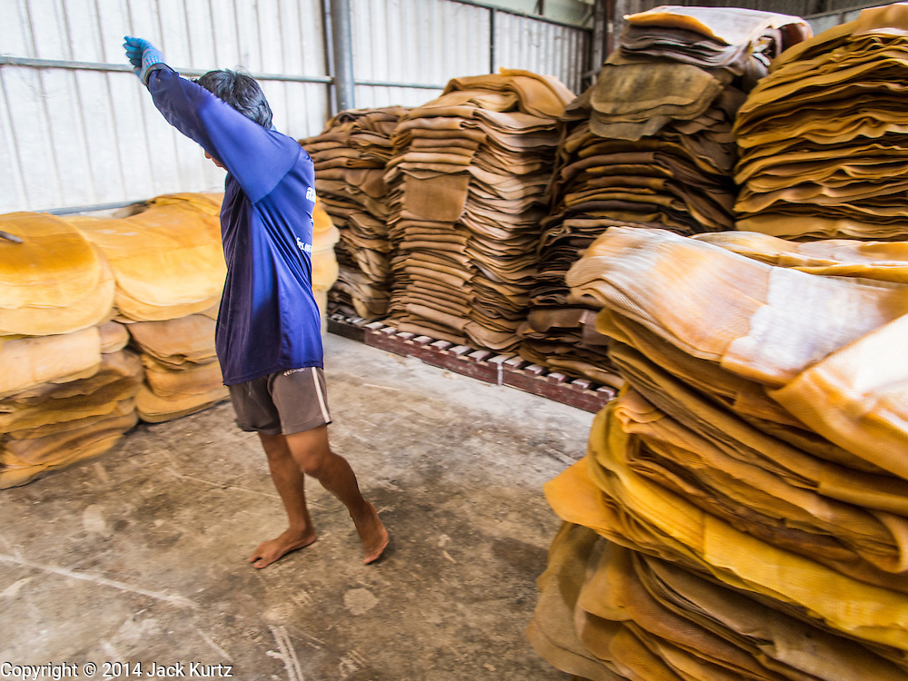 """15 DECEMBER 2014 - CHUM SAENG, RAYONG, THAILAND: A worker wipes his brow while stacking rubber sheets at a business that buys rubber from farmers in Chum Saeng, Thailand. Thailand is the second leading rubber exporter in the world. In the last two years, the price paid to rubber farmers has plunged from approximately 190 Baht per kilo (about $6.10 US) to 45 Baht per kilo (about $1.20 US). It costs about 65 Baht per kilo to produce rubber ($2.05 US). Prices have plunged 5 percent since September, when rubber was about 52Baht per kilo. Some rubber farmers have taken jobs in the construction trade or in Bangkok to provide for their families during the slump. The Thai government recently announced a """"Rubber Fund"""" to assist small farm owners but said prices won't rebound until production is cut and world demand for rubber picks up.     PHOTO BY JACK KURTZ"""